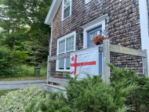 A cedar-shingled house with white trim has the Mi'kmaq Grand Council flag hanging from the wooden railing on the porch.