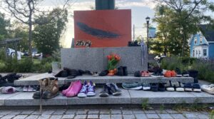 Many pairs of children's shoes are laid in rows around a granite memorial in a town square.