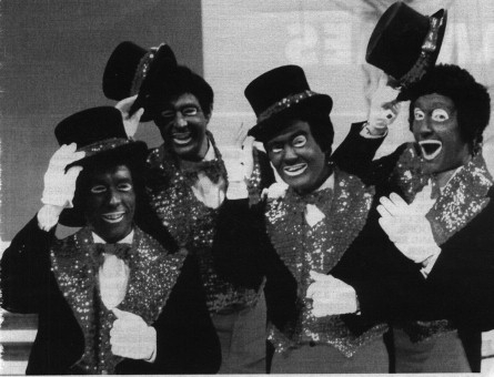 Four white men making asses of themselves dressed in blackface and ridiculous sparkly costumes, top hats, and white gloves.