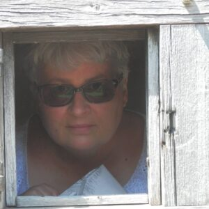 A photo of Nadine Hardiman, wearing sunglasses (it's a bright day) and peering from inside her house through a small window at the camera outside.