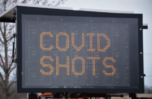 An outdoor electronic sign reads Covid shots in yellow capital letters on a dark background.