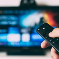 A photo of a man's hand holding a remote pointed at a TV.