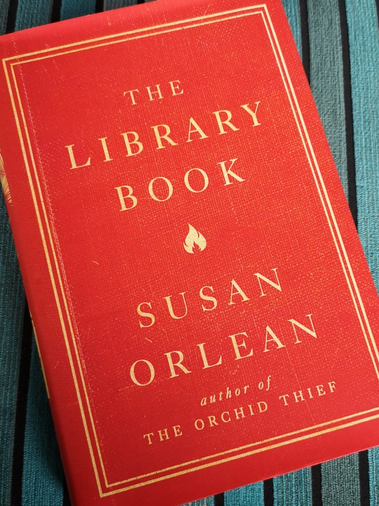 Hardcover copy with red dustjacket of The Library Book, by Susan Orlean