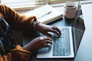 A photo of a Black woman's hands while she uses a Mac laptop. she has a lovely orange sweater, and there's a cup of tea and a notebook beside her, and the light from the window on her left.