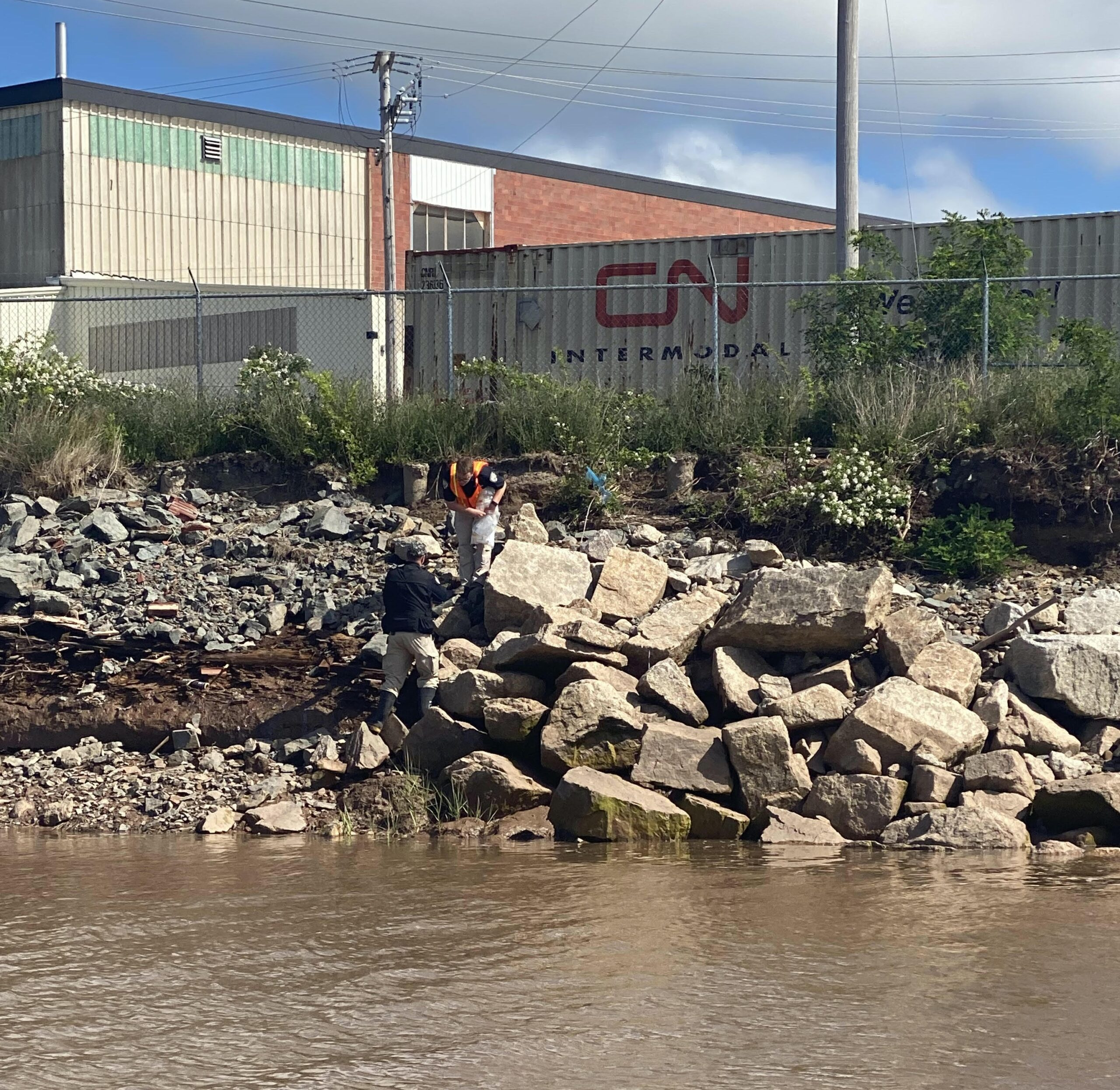 Water, pile of rocks, CN railcar, and building in background.