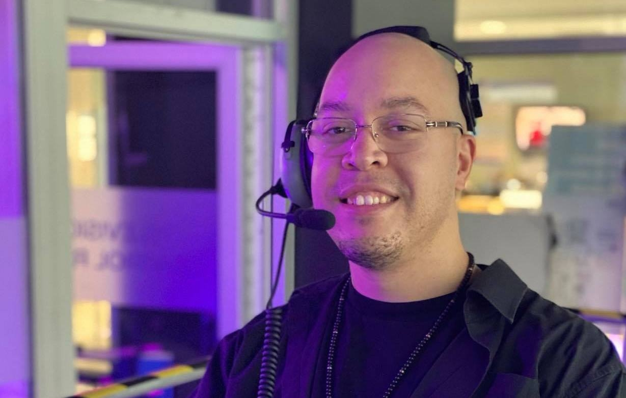 Matthew Byard, in a recording studio. He's smiling at the camera, wearing a headset. He's got wire-framed glasses, a shaved head and the beginnings of a small beard on his chin.