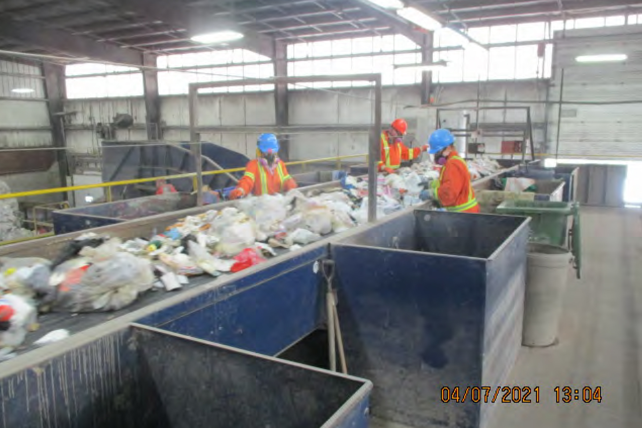In a grainy photo, time-stamped April 7, 2021 at 13:04, three workers in orange high-visibility suits wearing hard hats and masks sort garbage on a conveyer belt.