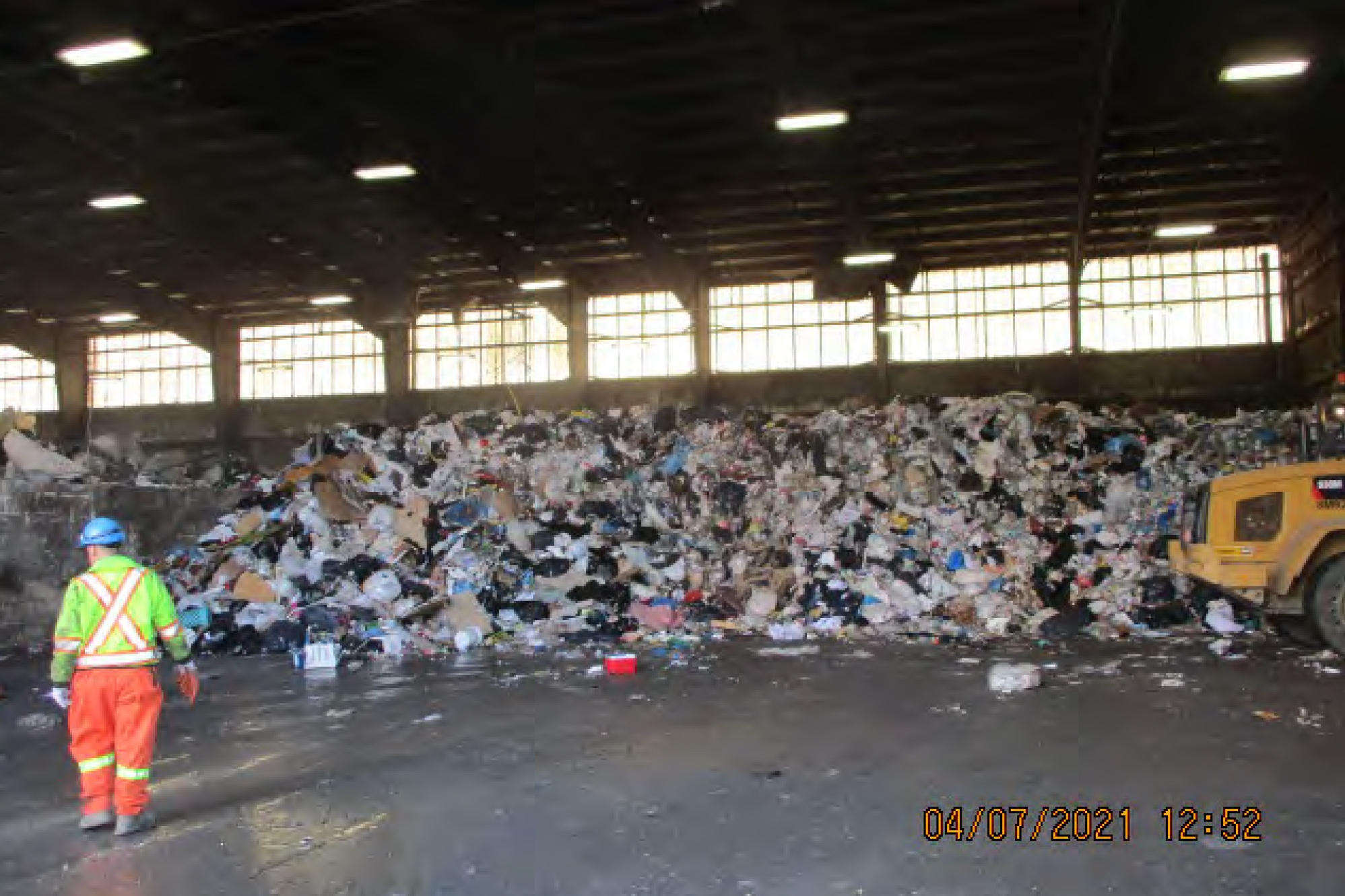 In a grainy photo, time-stamped April 7, 2021 at 12:52, a big pile of garbage is seen stacked in a warehouse-type room with lights on the ceiling and windows in the background stretching across the wall. On the left, a worker wearing high-visibility blue, fluorescent yellow and orange clothing walks toward the garbage. On the right, the rear end of a front-end loader is visible.