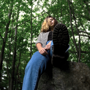 Dana Beeler, sitting on a rock in the forest