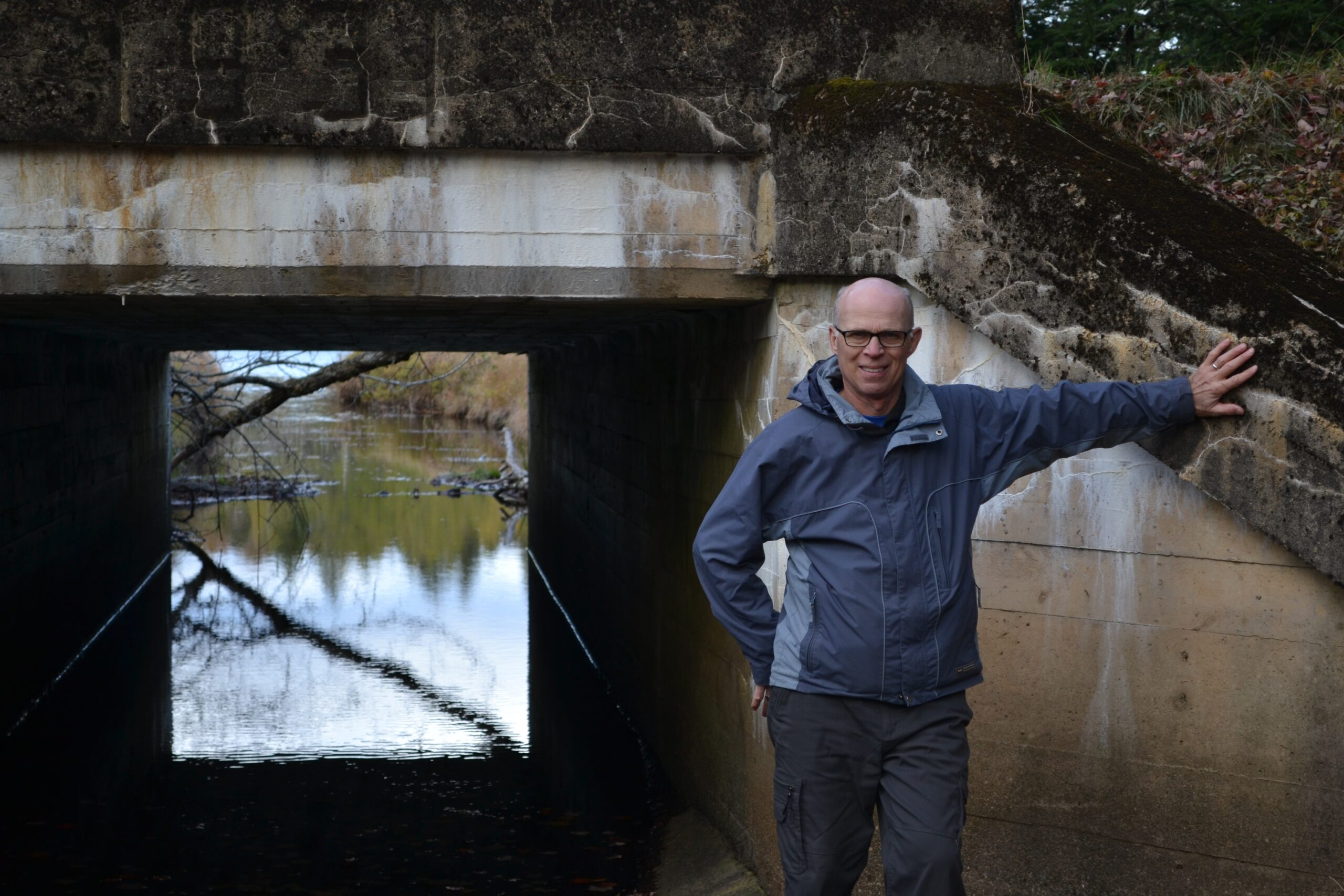 Bald man in a rain jacket standing in front of a concrete abutment.