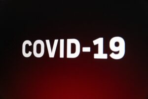 COVID 19 written in white capital letters on a dark red background.