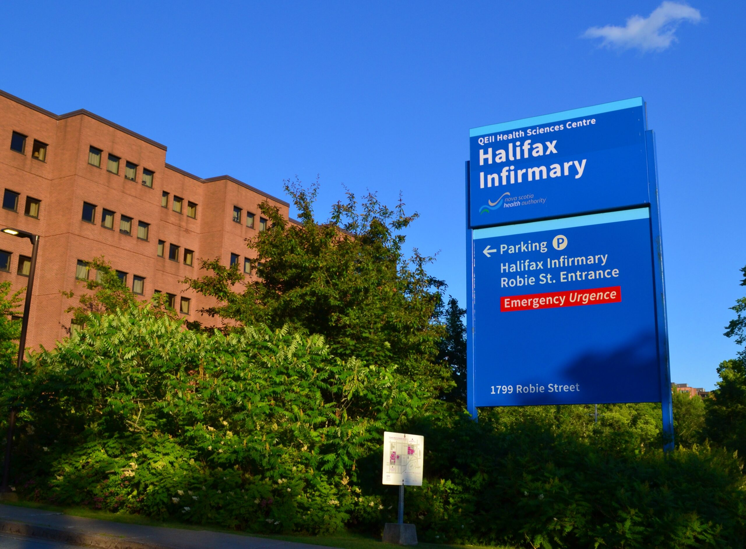 Bright blue Halifax Infirmary signage against a blue sky.
