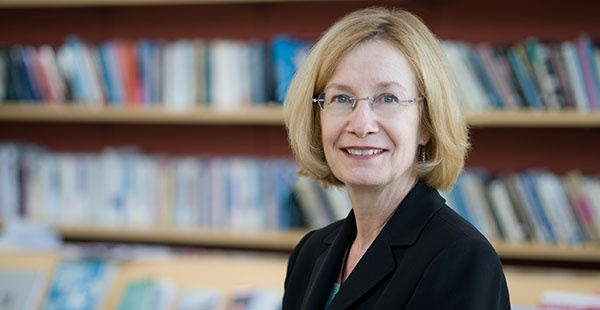 Headshot of a middleaged woman with shortish blonde hair, seated in front of a bookshelf. She is wearing glasses and smiling at the camera.