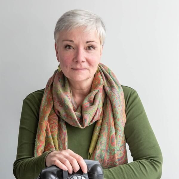 Distinguished looking woman with short white hair, in a long-sleeved green shirt with a scarf, in front of a neutral background.