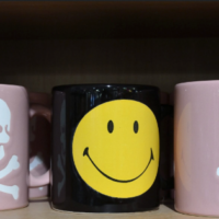 Three mugs on a shelf. The ones on the left and right are pink with white skulls and crossbones, the one in the middle is black with a bright yellow smiley face.