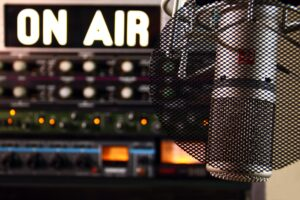 Inside a radio studio: a closeup of the microphone, with a lit up On Air sign in the background.