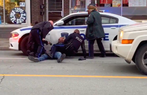 In a screenshot from a video, four police officers surround a Black man who's on the ground, pressed up against a white police car with blue decals and flashing lights on. One of the officers on the left is holding a Taser. Another on the left is leaning over the first officer. On the right, one officer has his leg on top of the man as another officer watches. The scene is captured from across the street. There's a vehicle in the right of the frame stopped. In the background, the word bagel is seen on a round decal on a shop window.