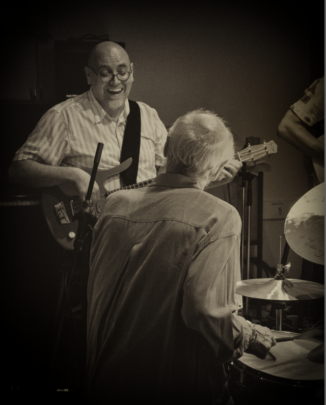 Man playing guitar and smiling, looking at an older drummer (we see the back of the drummer's head)