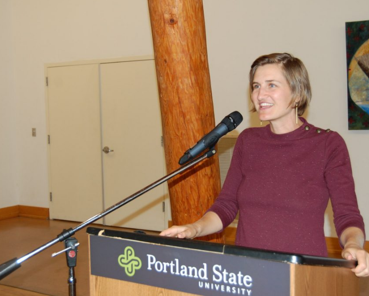 Smiling woman in her 30s standing at a podium, speaking into a microphone. The podium has a banner that says Portland State University