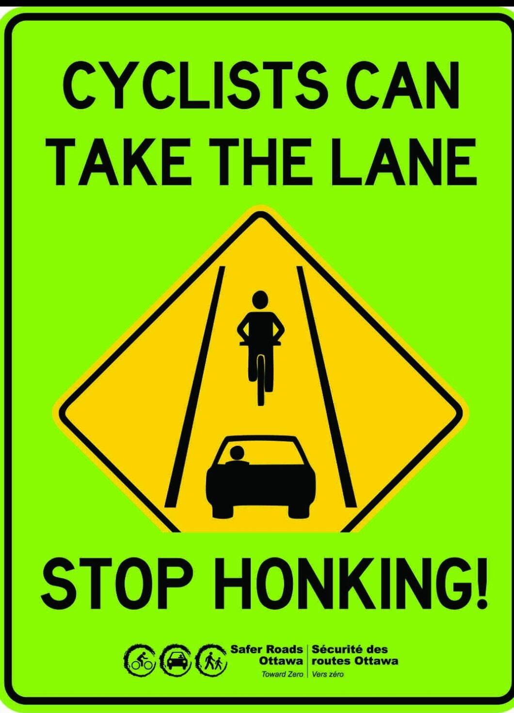 """Road sign showing a yellow diamond with a bicycle and car. Text says: Cyclists can take the lane. Stop honking!"""""""
