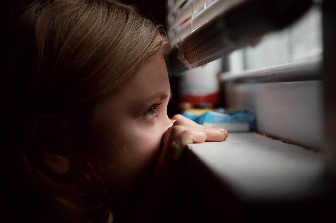A small girl peeks below a venetian blind, out a window.