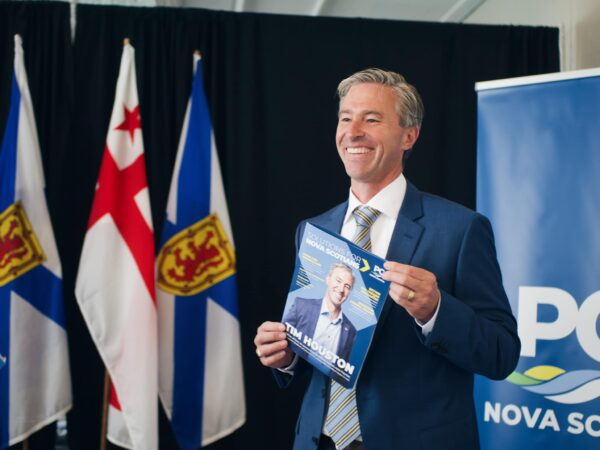 Smiling man in blue suit stands in front of Nova Scotia and Mi'qmac flags, holding a document with himself on the cover.