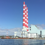 The red and white stacks of the Tufts Cove generating station on a bright sunny day