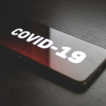 A rectangular dark red button reading COVID 19 in white lettering