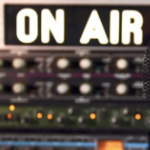 """the words """"On Air"""" lit up on a sign in a radio studio"""