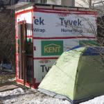 A tent sits beside a wooden homeless shelter