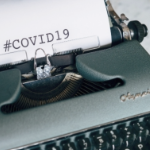 a green typewriter with the phrase COVID 19 typed on the white paper
