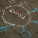 a cartoon of the coronavirus drawn in coloured chalk on a brick sidewalk