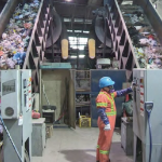 A man sorts garbage on an inclined conveyor belt