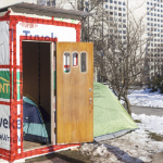 An emergency shelter in the winter, with a tent inside and another outside.