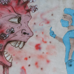 """A mural with a large coronavirus with teeth, and a nurse in full PPE giving it a """"come here"""" finger gensture, or possible the middle finger."""