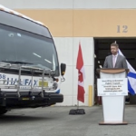 Premier Rankin stands at a podium beside a bus.
