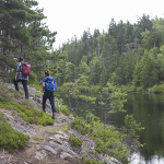 Two people hike on a trail next to a lake
