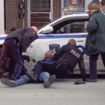A Black man is seated on the street with his back against a police car while one cop sits on top of him, another cop tasers him, one leans over him and one stands by watching.