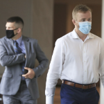 Two men in a hallway. One wears a suit and tie, one wears a dress shirt with no tie or jacket, and both wear masks.