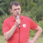 Jacob Killawee, talking into a microphone, wearing a red golf shirt with his own campaign button on the chest.