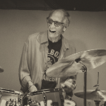 Gerry Granelli, laughing while he plays the drums. Photo by Kent Martin.