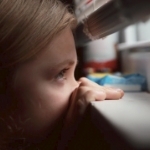 A young girl peeks out a window