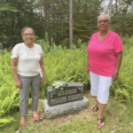 Irma Olivier Riley and Debra Lucas standing next to a headstone in a ferny area