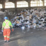 A man in front of a mountain of rubbish inside a warehouse at Otter Lake dump