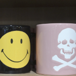 a smiley face mug next to one with a skull and crossbones.