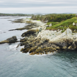 An aerial shot of a point of rocky shore at Owls' Head, on an overcast day.