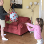 A young girl hits a birthday piniata in the shape of the coronavirus