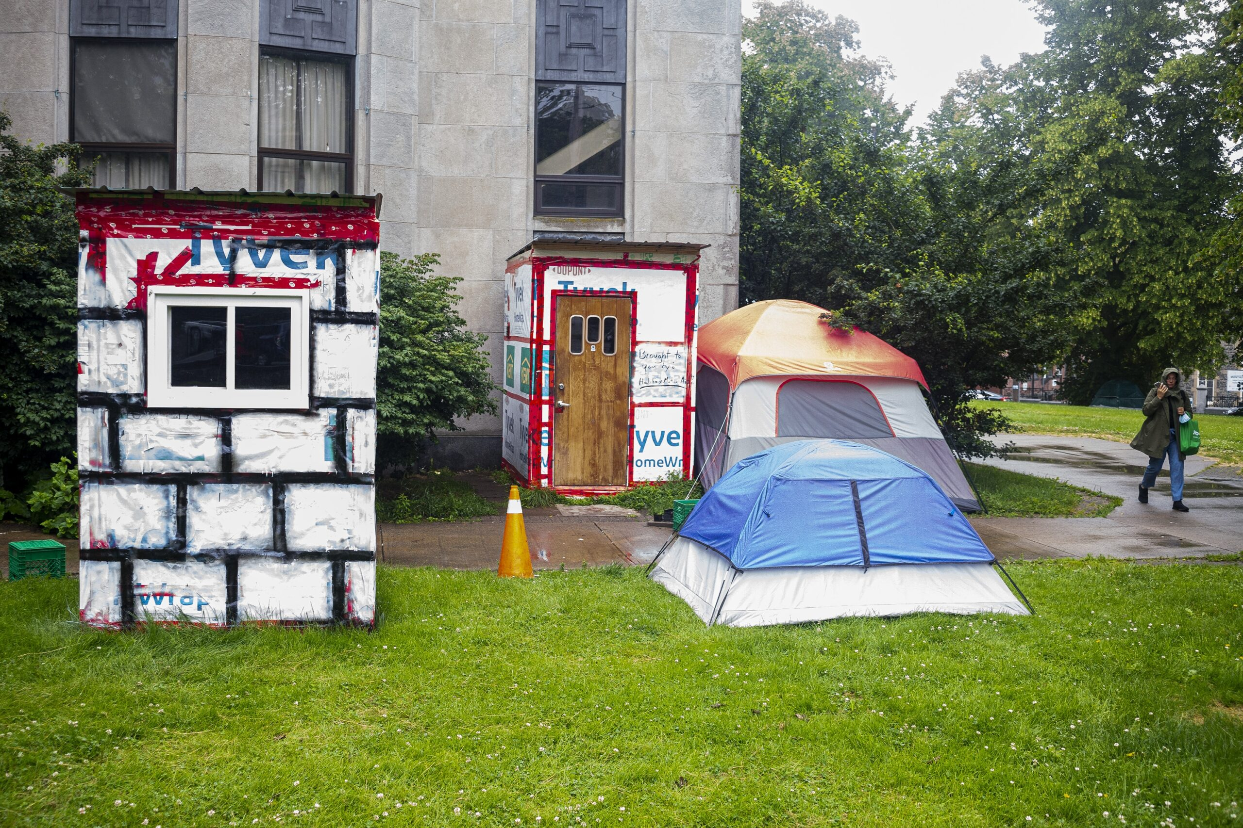 On a rainy day, two crisis shelters and two tents are seen on grass outside a sandstone building. The shelter on the left is white with a small window on the visible side, covered in Tyvek house wrap painted with a black grid. In the centre, there's another shelter, with a wooden door with three small windows. Next to that shelter, there's a red and grey tent. In front of the red and grey tent there's a blue and grey tent. To the right, a woman wearing a three-quarter length coat and carrying a green reusable grocery bag walks by talking on a cellphone on speaker.
