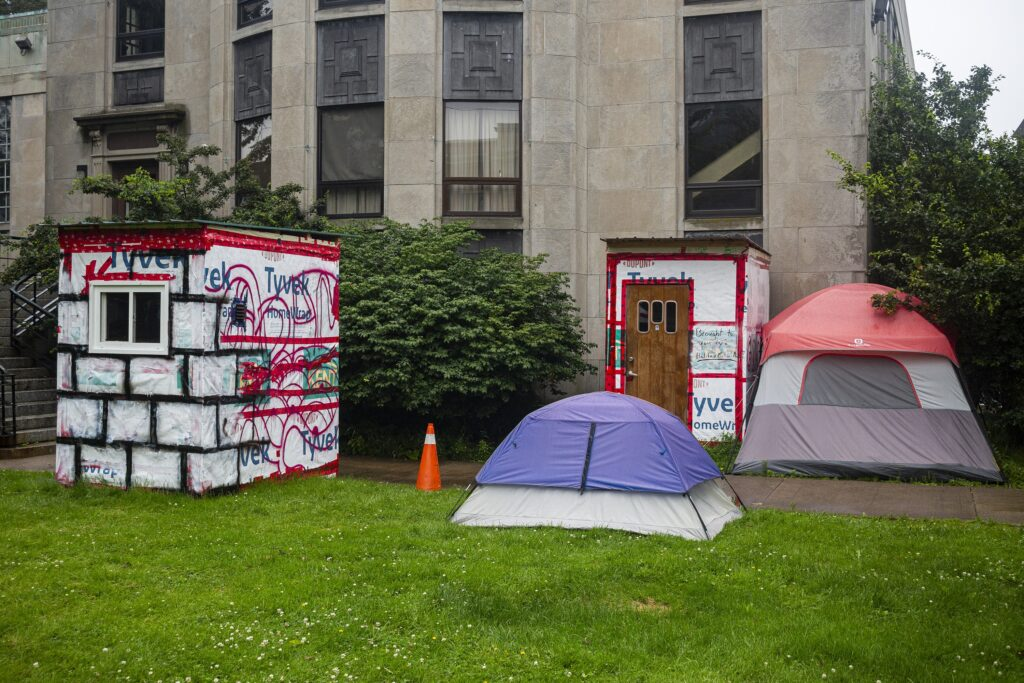 On a rainy day, two crisis shelters and two tents are seen on grass outside a sandstone building. The shelter on the left is white with a small window on one side, covered in Tyvek house wrap painted with a black grid on one side and red scribbles on the other side. In the centre, there's a purple and grey tent in front of another shelter, with a wooden door with three small windows. Next to that shelter, there's a red and grey tent.