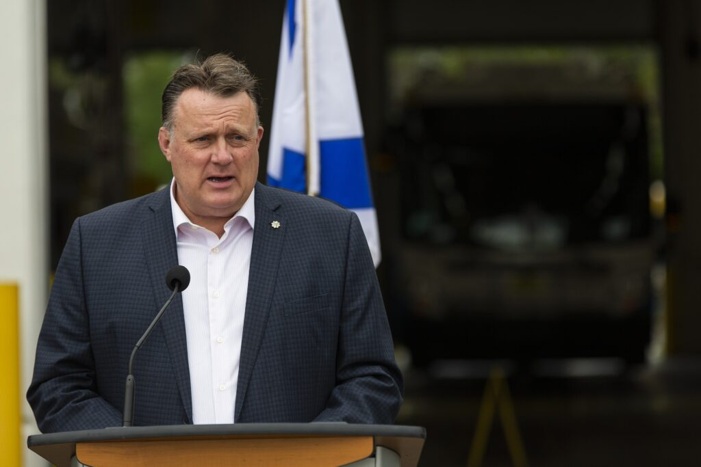 A man wearing a dark suit and white shirt speaks at a podium and gestures to his right. In the background is part of a Nova Scotia flag, blue and white, and a bus in the dark.